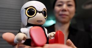 This picture taken on September 27, 2016 shows a Toyota employee displaying the company's new communication robot 'Kirobo Mini' during a press preview in Tokyo. Equipped with artificial intelligence and a built-in camera, the robot is capable of recognising the face of the person speaking to him and responding in unscripted conversation or even starting a chat. TOSHIFUMI KITAMURA / AFP