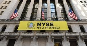 A Snap Inc. (Snapchat) trader stands in front of New York Stock Exchange on Wall Street in New York January 25 , 2017. The Dow Jones Industrial Average, the most famous equity index benchmark on Wall Street shot above 20,000 for the first time at the open Wednesday. TIMOTHY A. CLARY / AFP